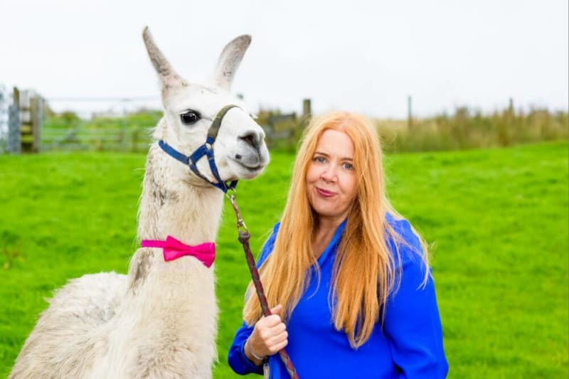Woman smiling into camera next to a llama in a bow tie.