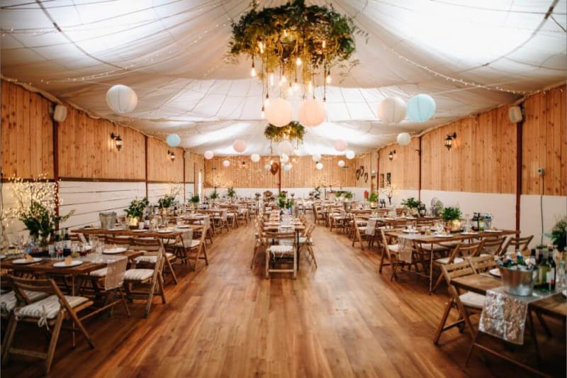 Inside of a wedding venue with tables and decorations set up for a wedding.