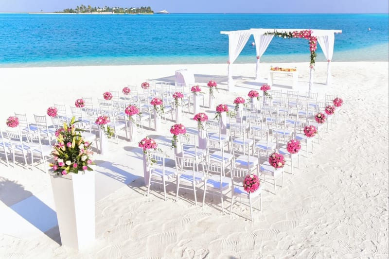 Pink flowers wedding chair decorations on white chairs for stunning beach wedding outdoors