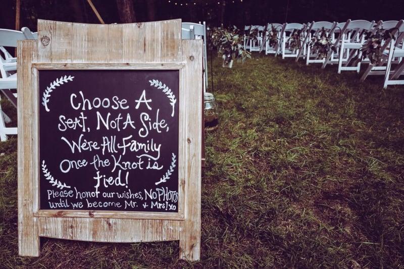 Wedding chalkboard sign next to wedding aisle at outdoor wedding