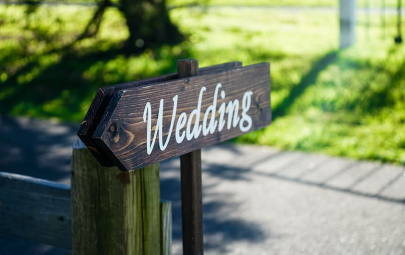 Wooden wedding sign outdoors showing wedding guests where wedding is