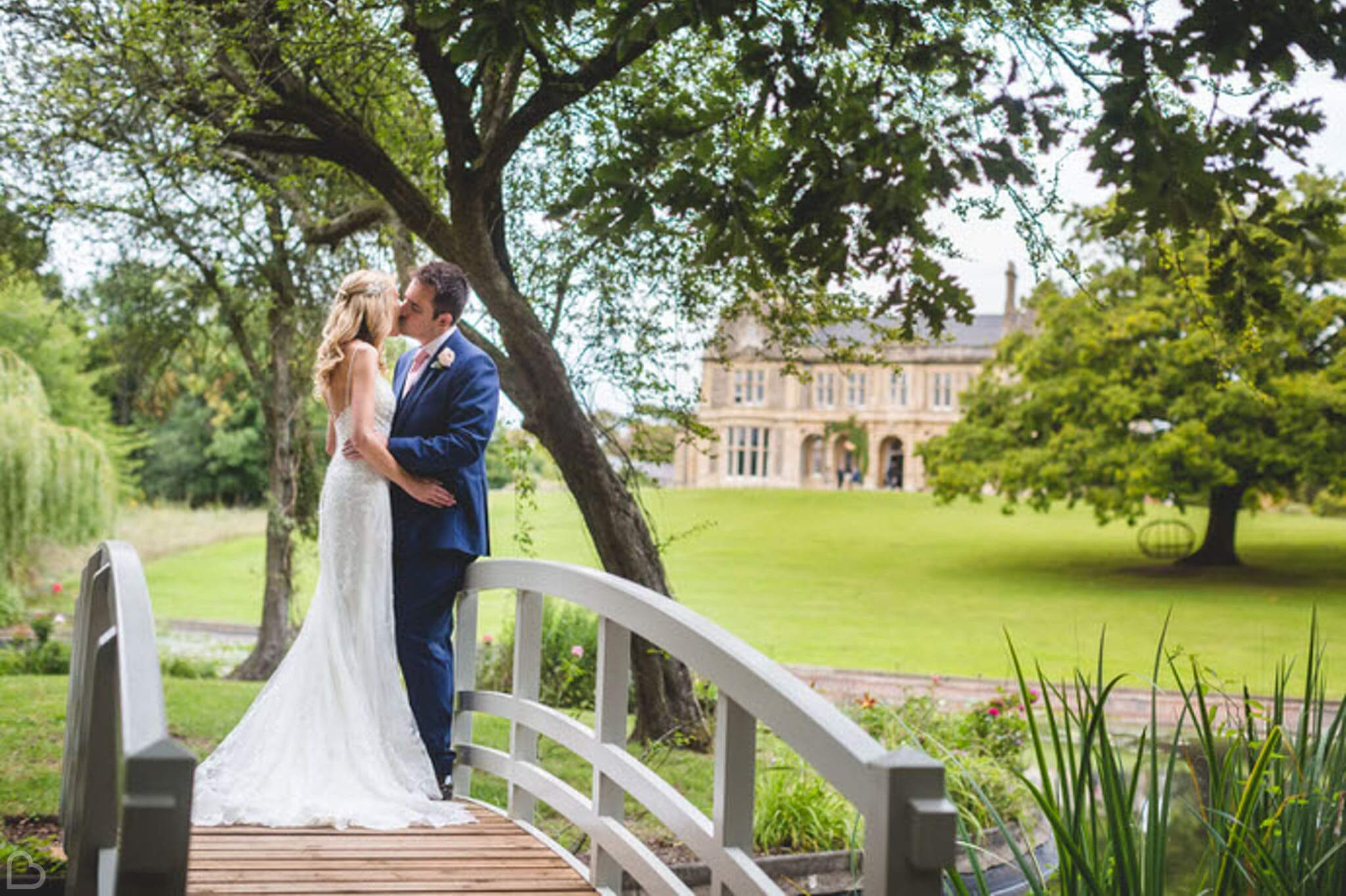 newlyweds kissing on a small bridge, at clevedon hall, a wedding venue in somerset.