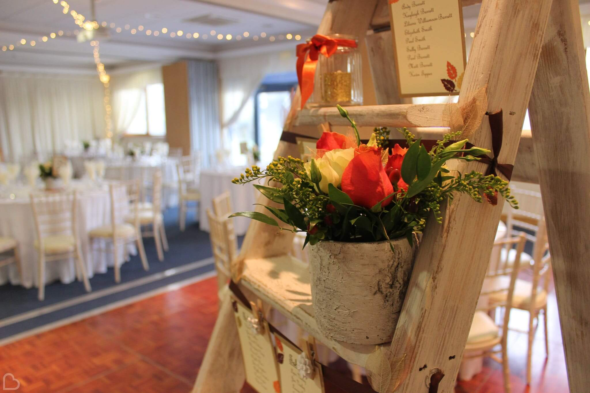 A flower pot is set up next to table seating charts at South Green Park Weddings, a beautiful wedding venue in Norfolk.
