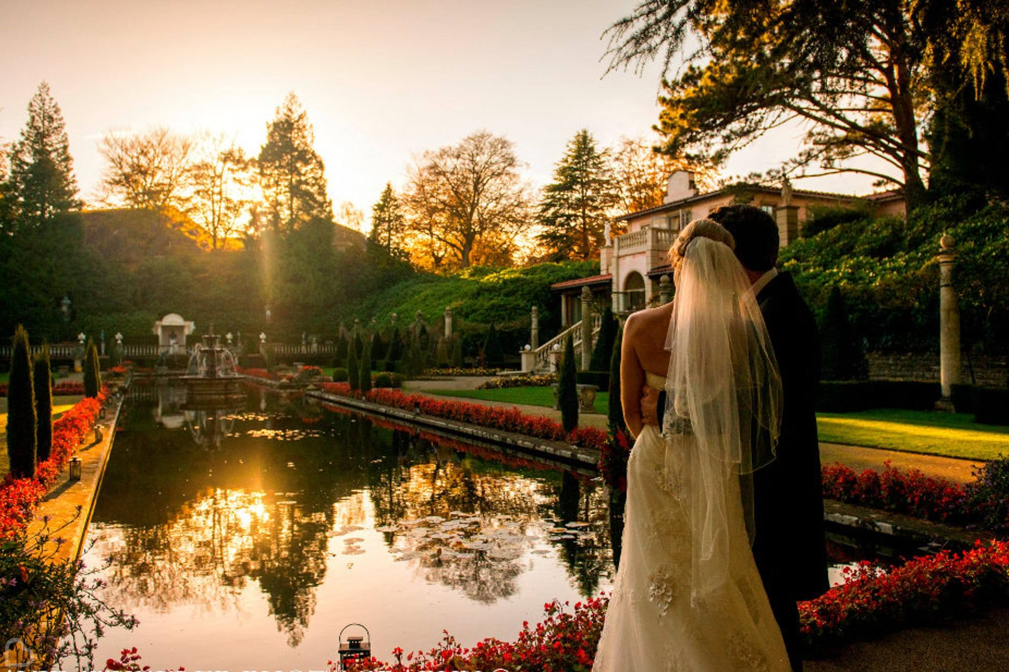 newlyweds embrace and watch the sunset over a lake at the italian villa at compton acres, a wedding venue in dorset.