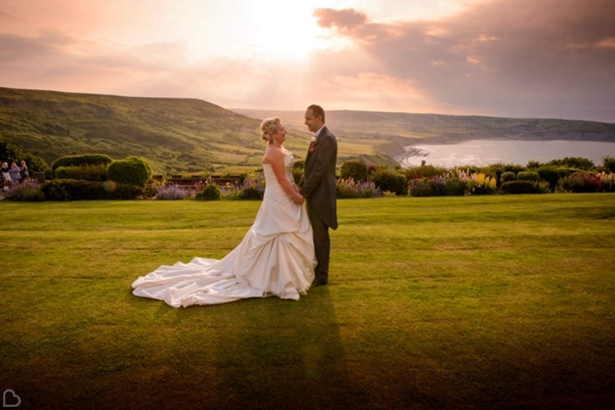 newlyweds hold hands at raven hall country house hotel, the sun shines over a lake in the background.