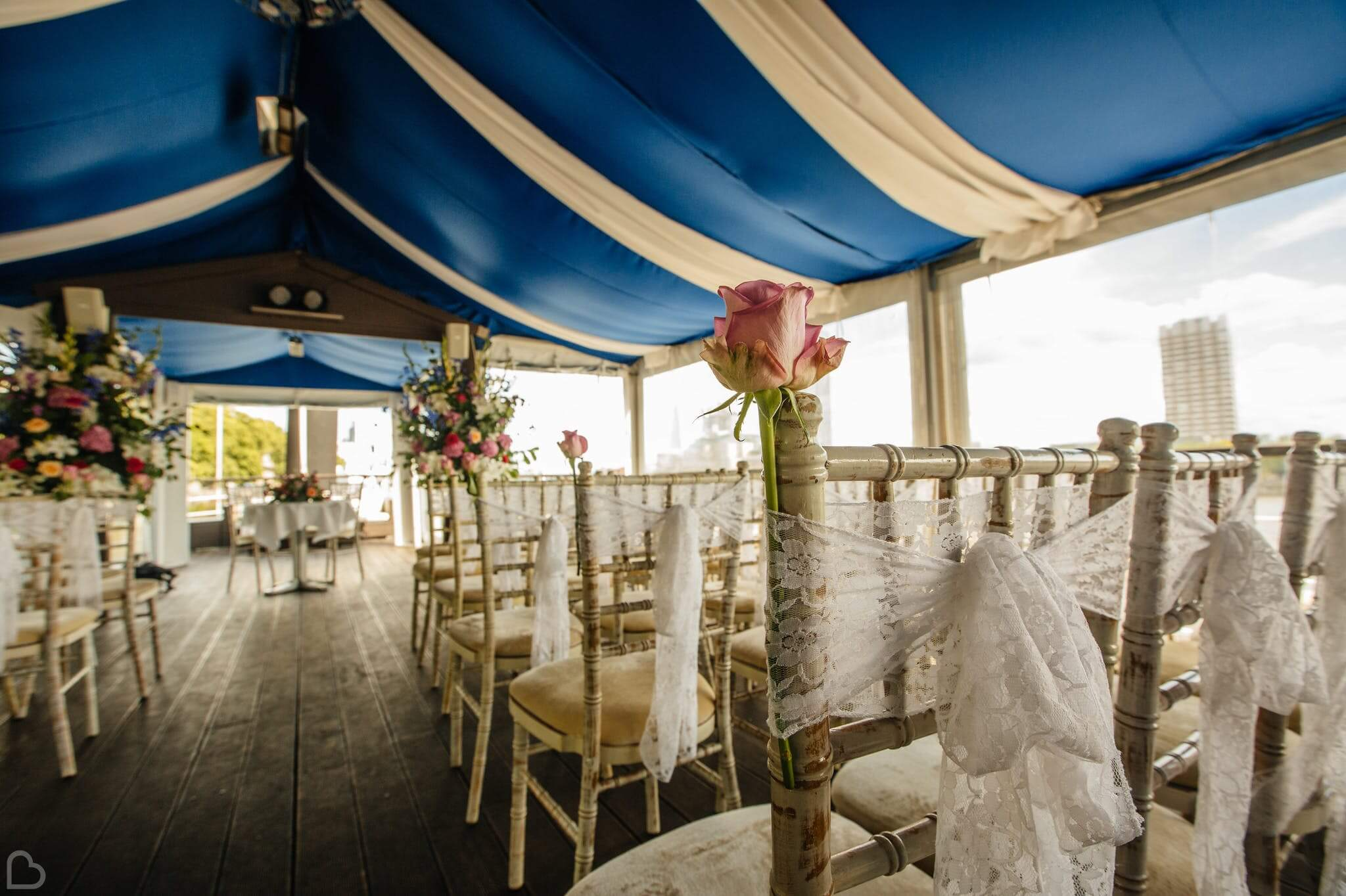 the yatch london chairs set up for a wedding ceremony with a rose and lace on each chair.
