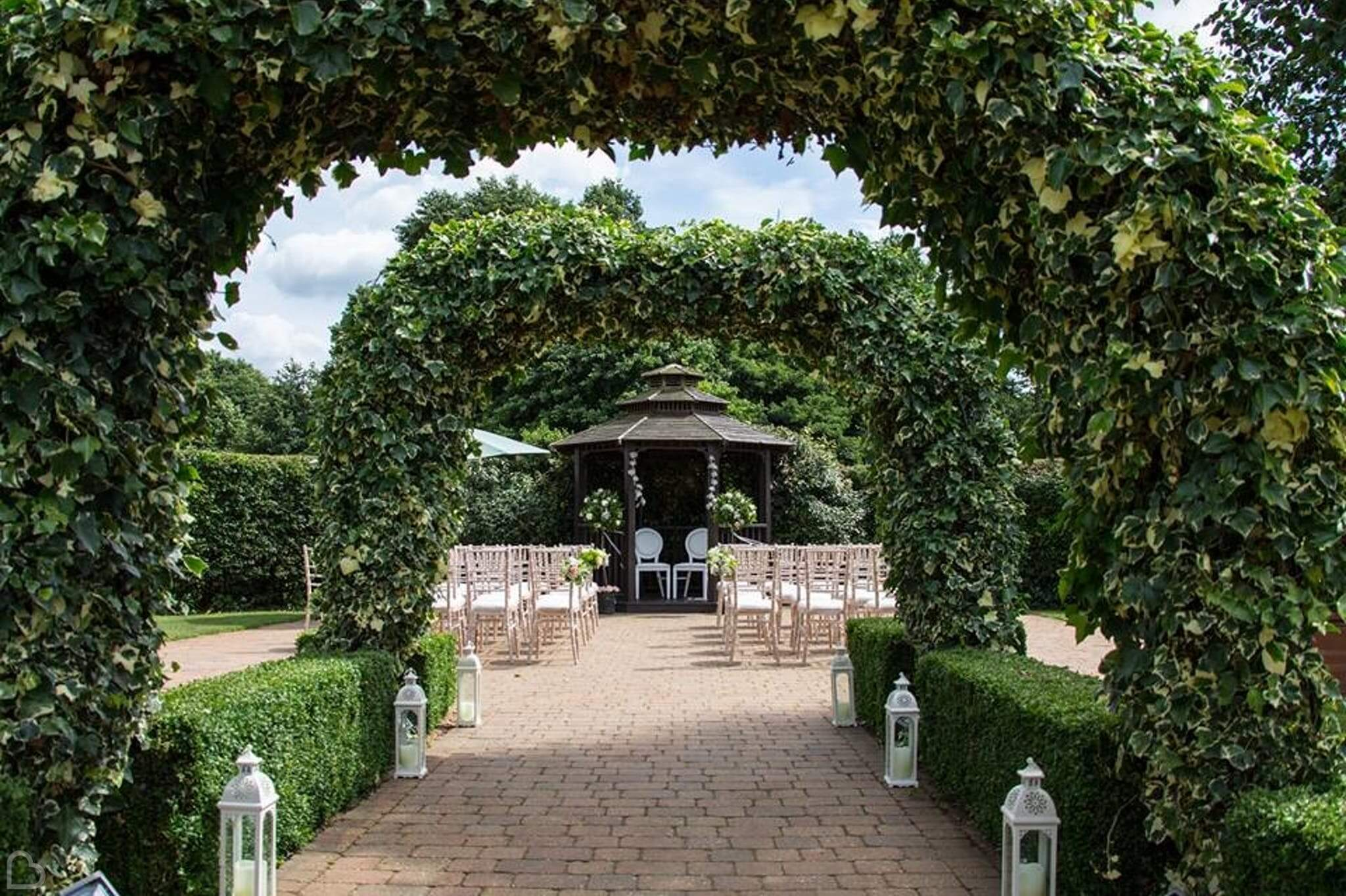 tewin bury farm hotel with green arches set up for wedding ceremony