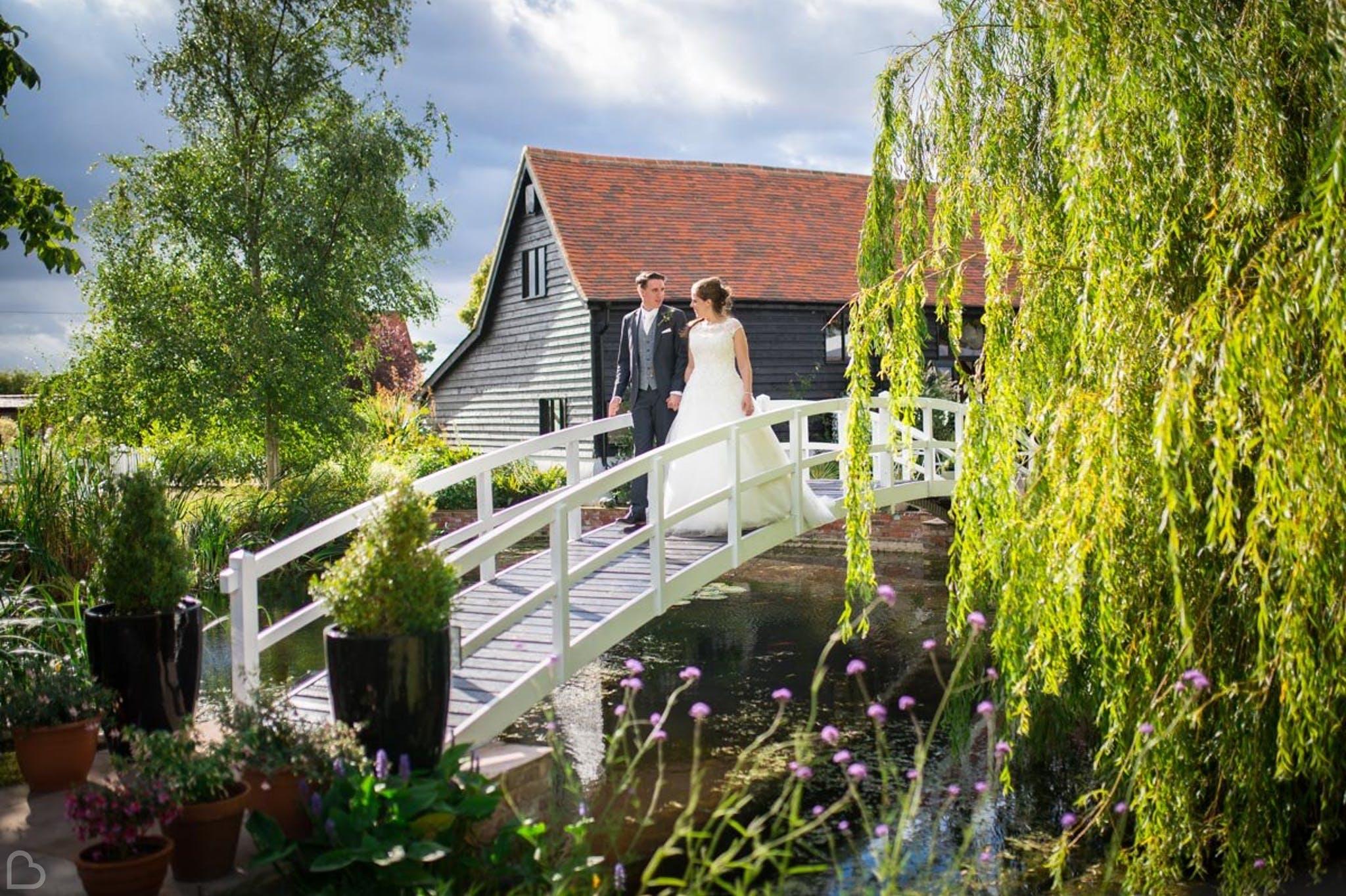 newlyweds crossing the bridge at high house weddings