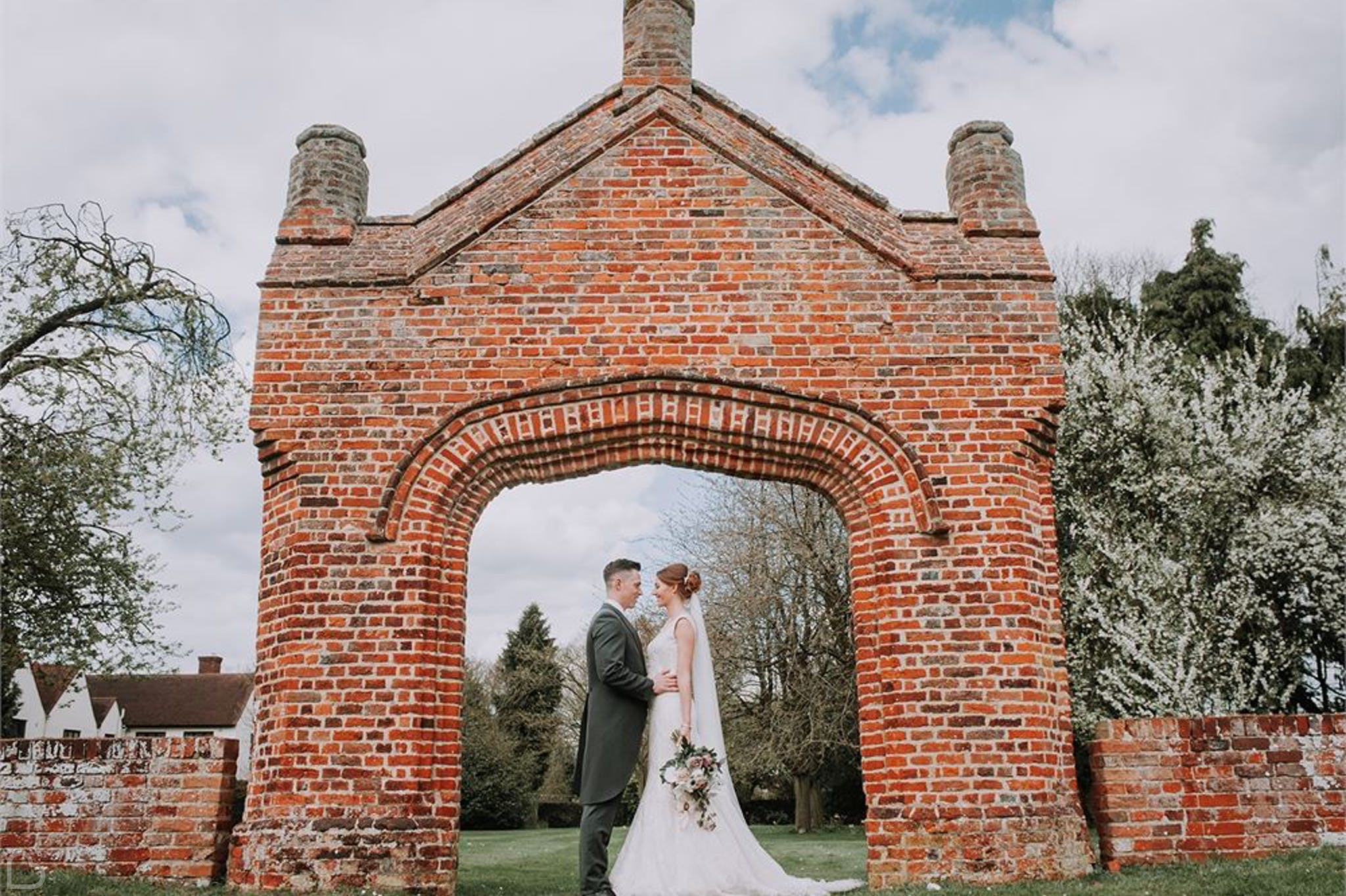 Newlyweds pose in arch at colville hall