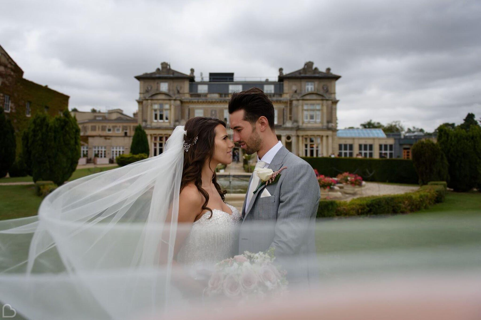 Newlyweds embrace is front of Down Hall Hotel & Spa