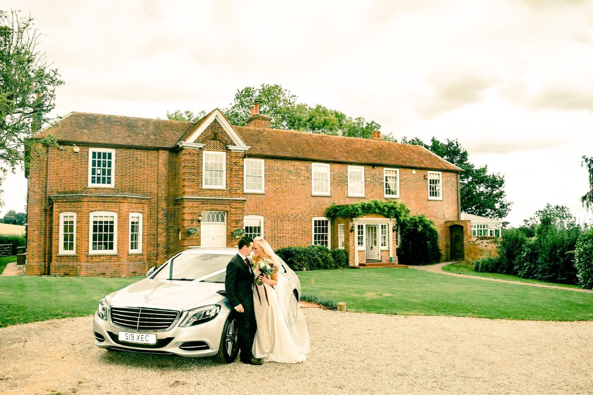 Newlyweds sit on wedding car in front of Downham Hall Wedding Venue in Essex