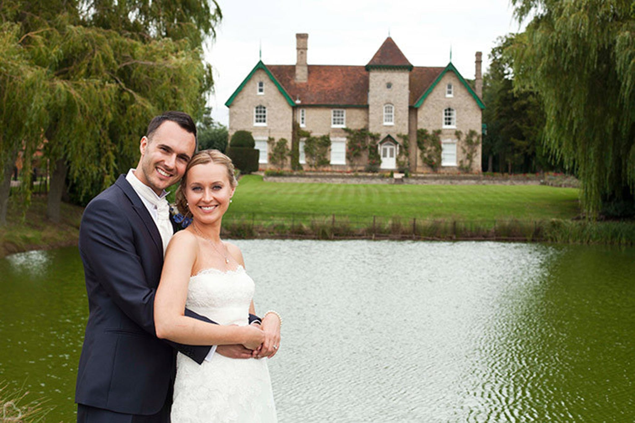 newlyweds pose in front of smeethan hall barn in essex
