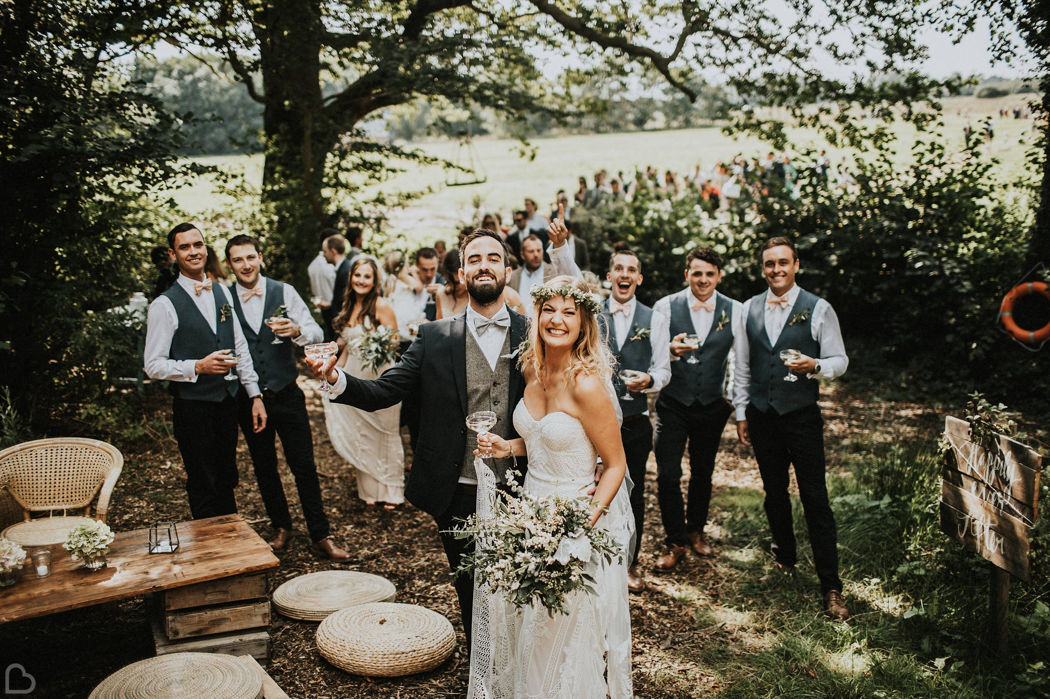 Bride with flower crown and groom celebrating their wedding outdoors with loved ones