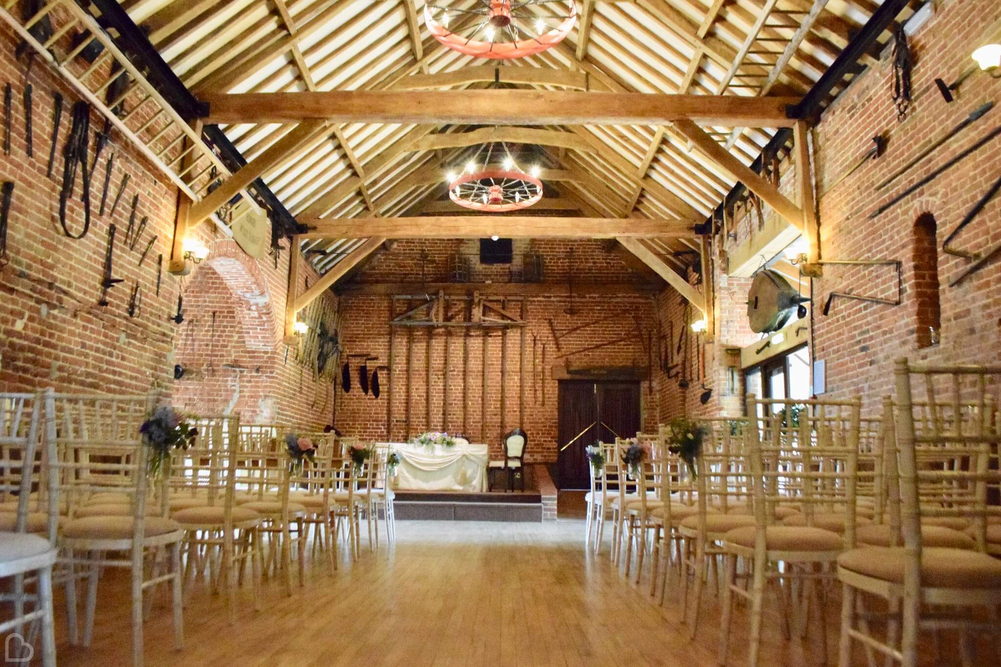 Hunters Hall barn set up with chairs and an altar, for a wedding ceremony.