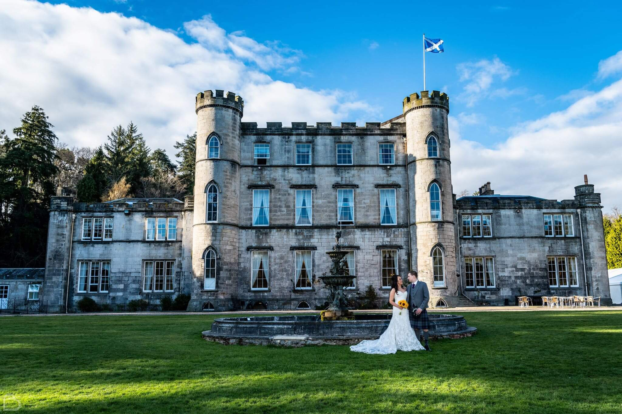 Newlyweds stand in front of Melville Castle, Edinburgh