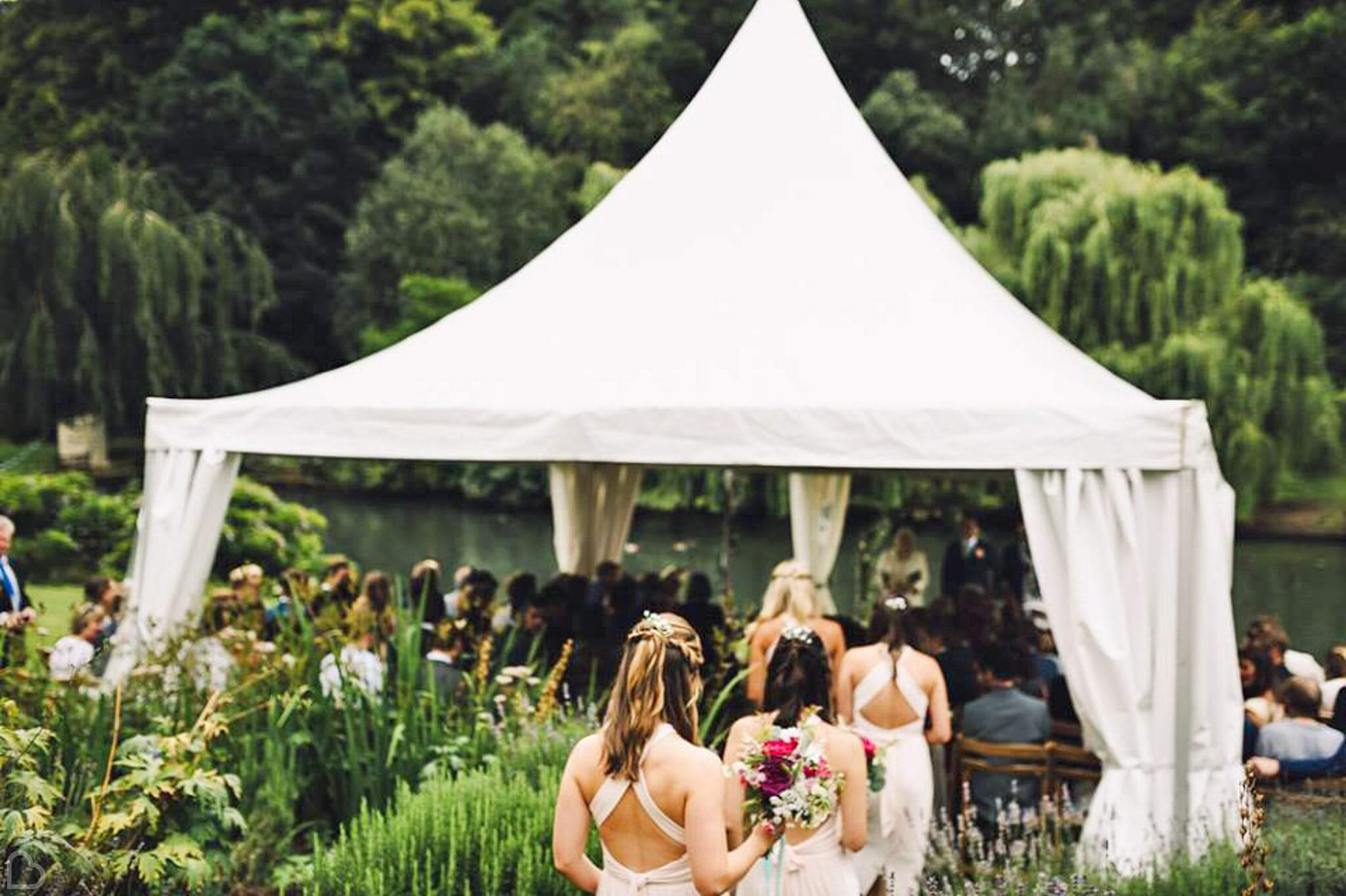 Busbridge Lakes in Surrey, bridemaids approach wedding ceremony by the lake.