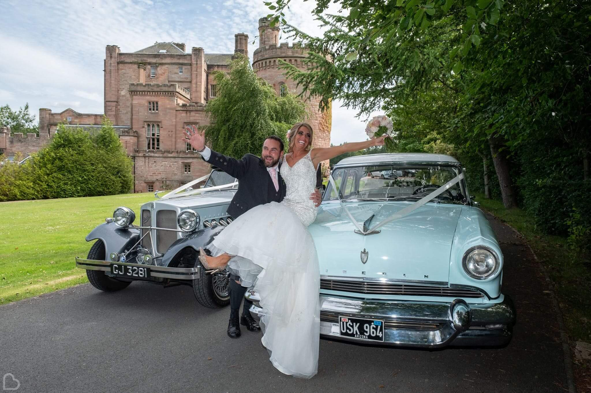 Newlyweds pose on their antique cars, in front of Dalhousie Castle.
