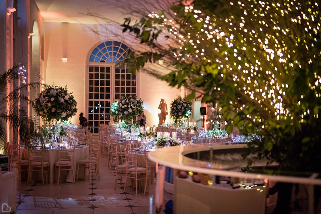 Wedding hall decorated with big flowers and fairy lights at kew gardens wedding venue.
