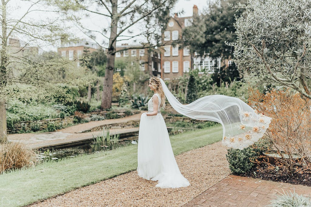 Bride poses amidst delicate autumn colours at the Chelsea Physic Garden.