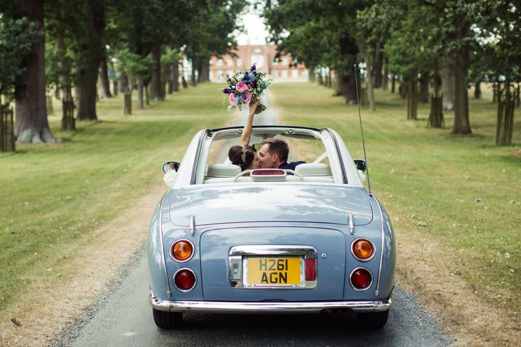 Newlyweds drive down the road at Helmingham Hall Gardens.