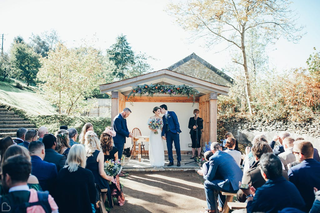 Groom tells bride a secret as they prepare as their outdoors wedding ceremony ends.