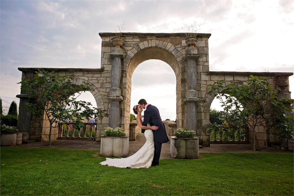 Newlyweds kiss in front of arched balcony, at flaxbourne gardens.