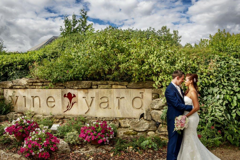 Newlyweds kiss outside the vineyard wedding venue in Berkshire
