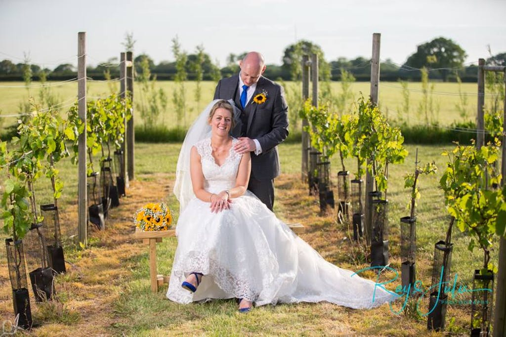 Bride and groom pose in the vineyard, the bride is sitting on a chair and the groom has his hand on her shoulder.