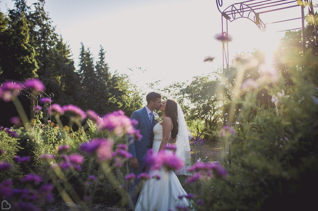 Newlyweds kiss in Hayne House garden.