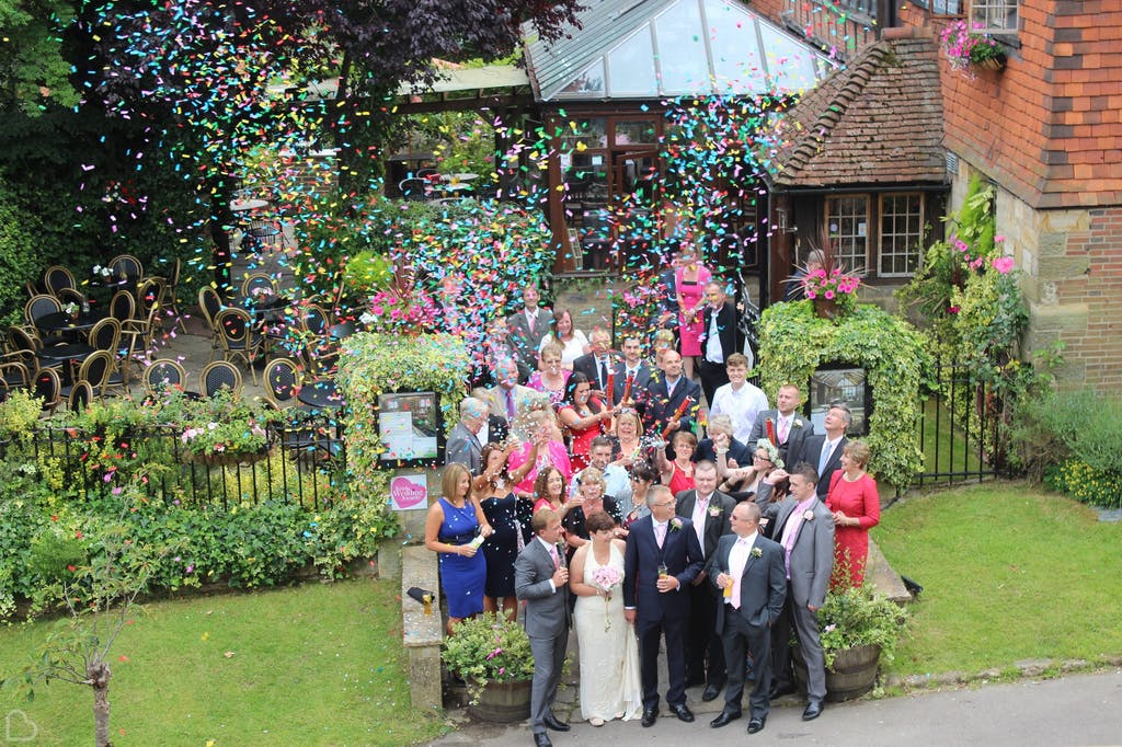 Wedding guests throw confetti outside The Barn. A cheap wedding venue in Kent.