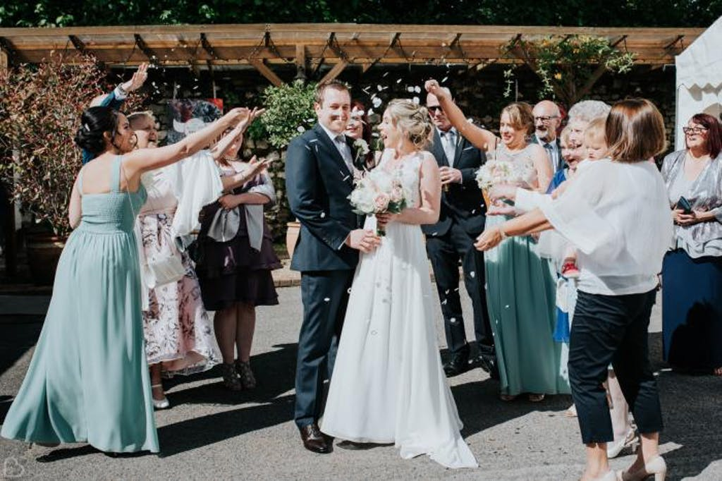 Guests throw rose petals at newlyweds.