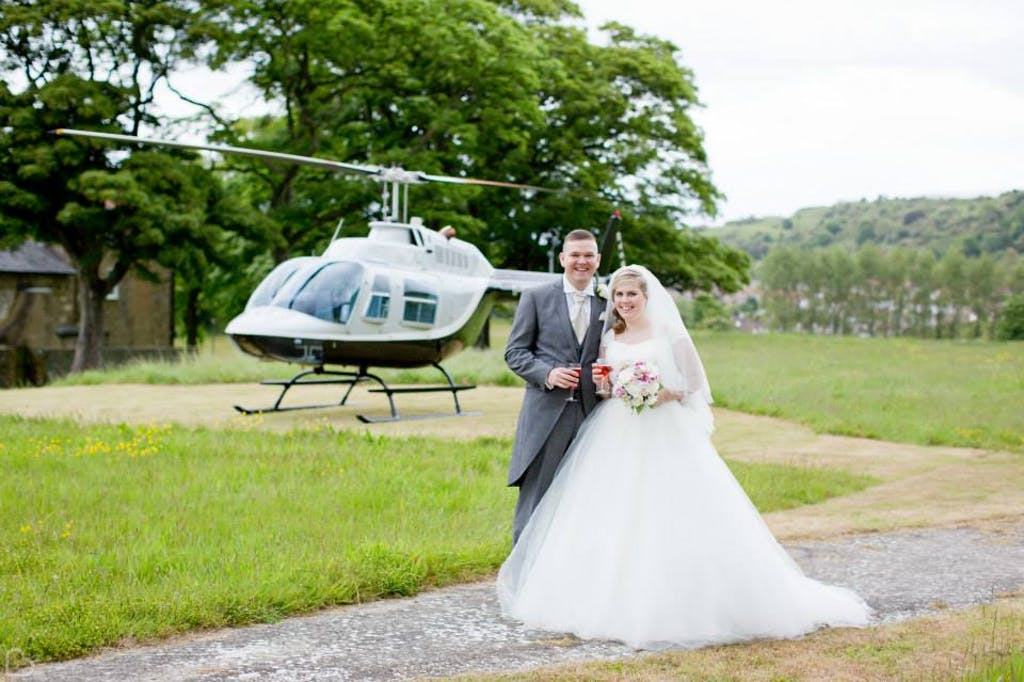 Newlyweds pose in front of helicopter at The Thatched Barn