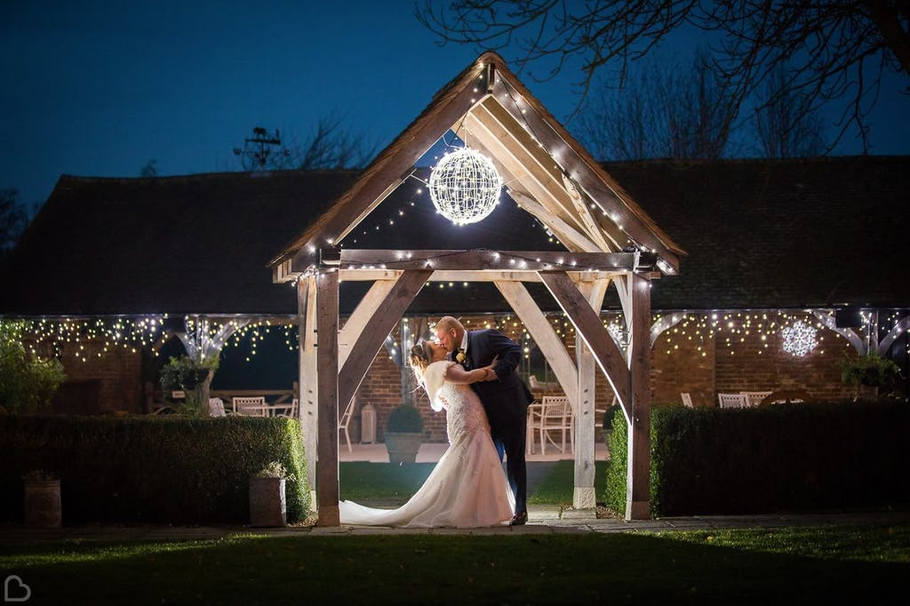 Newlyweds kiss surrounded by fairy lights in the garden.