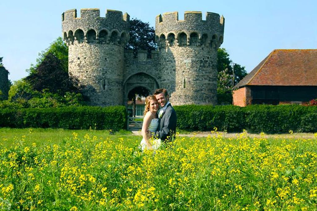 Newlyweds pose in front of castle tower at the cooling castle barn.
