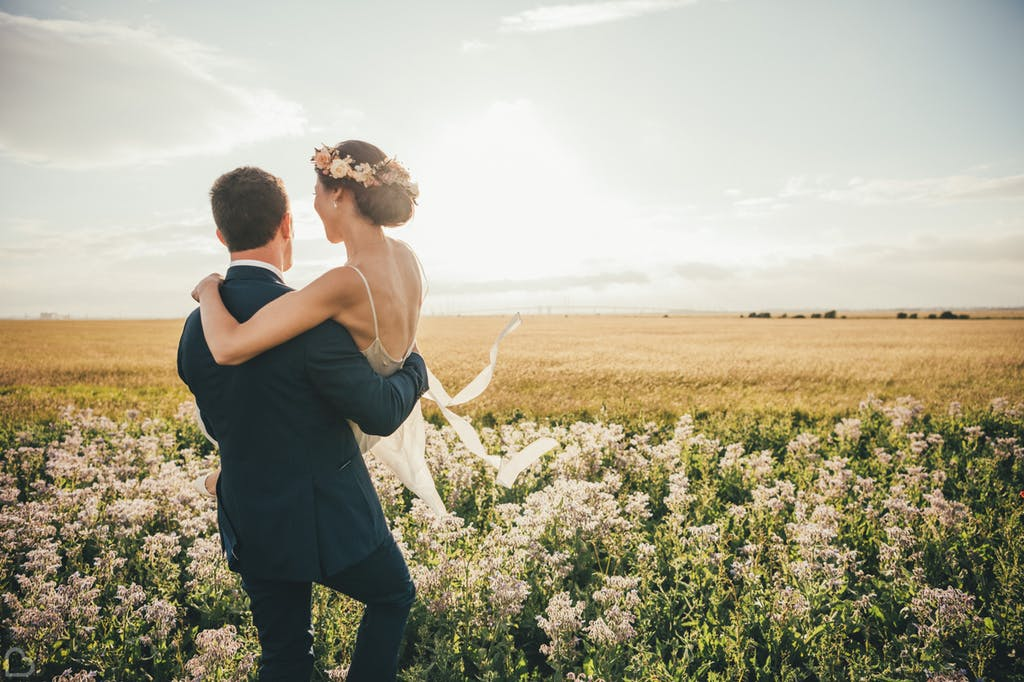 Newlyweds walking along the fields.