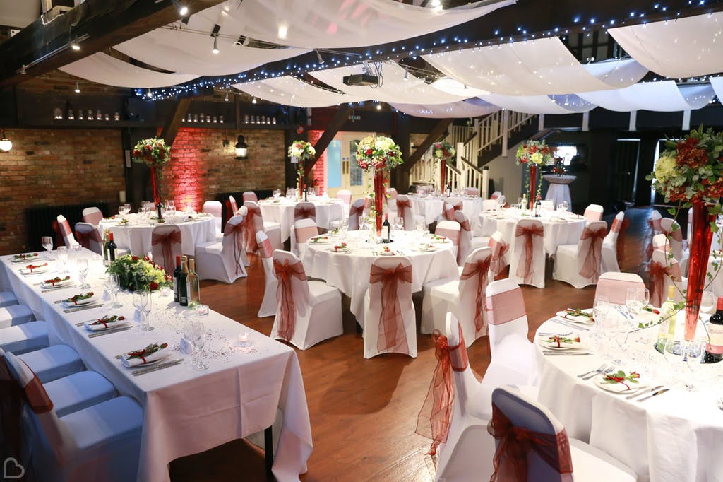 Wedding dinner set up with green and red tones at The Dickens Inn