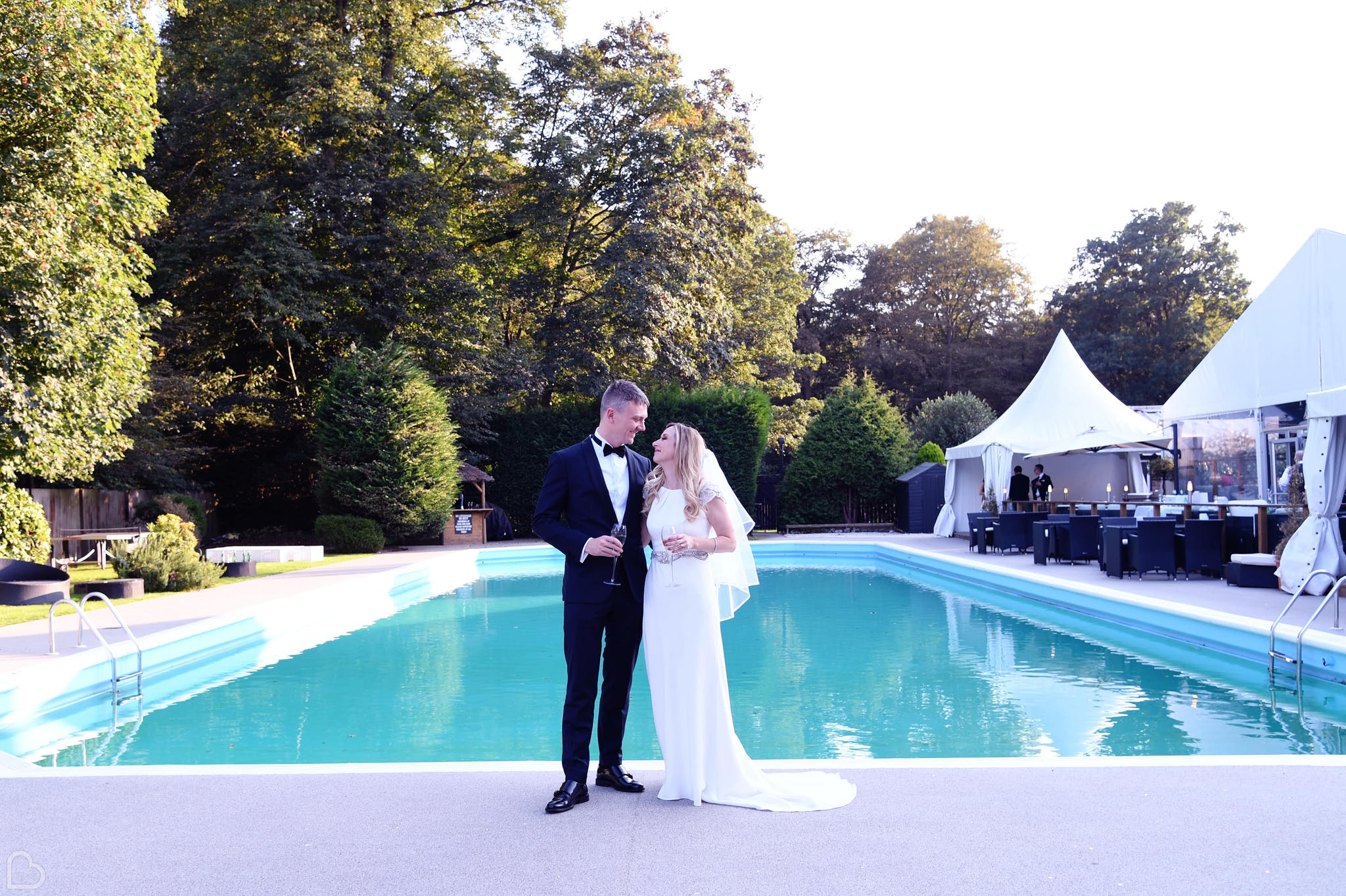 newlyweds pose in front of the pool and the kings oak hotel