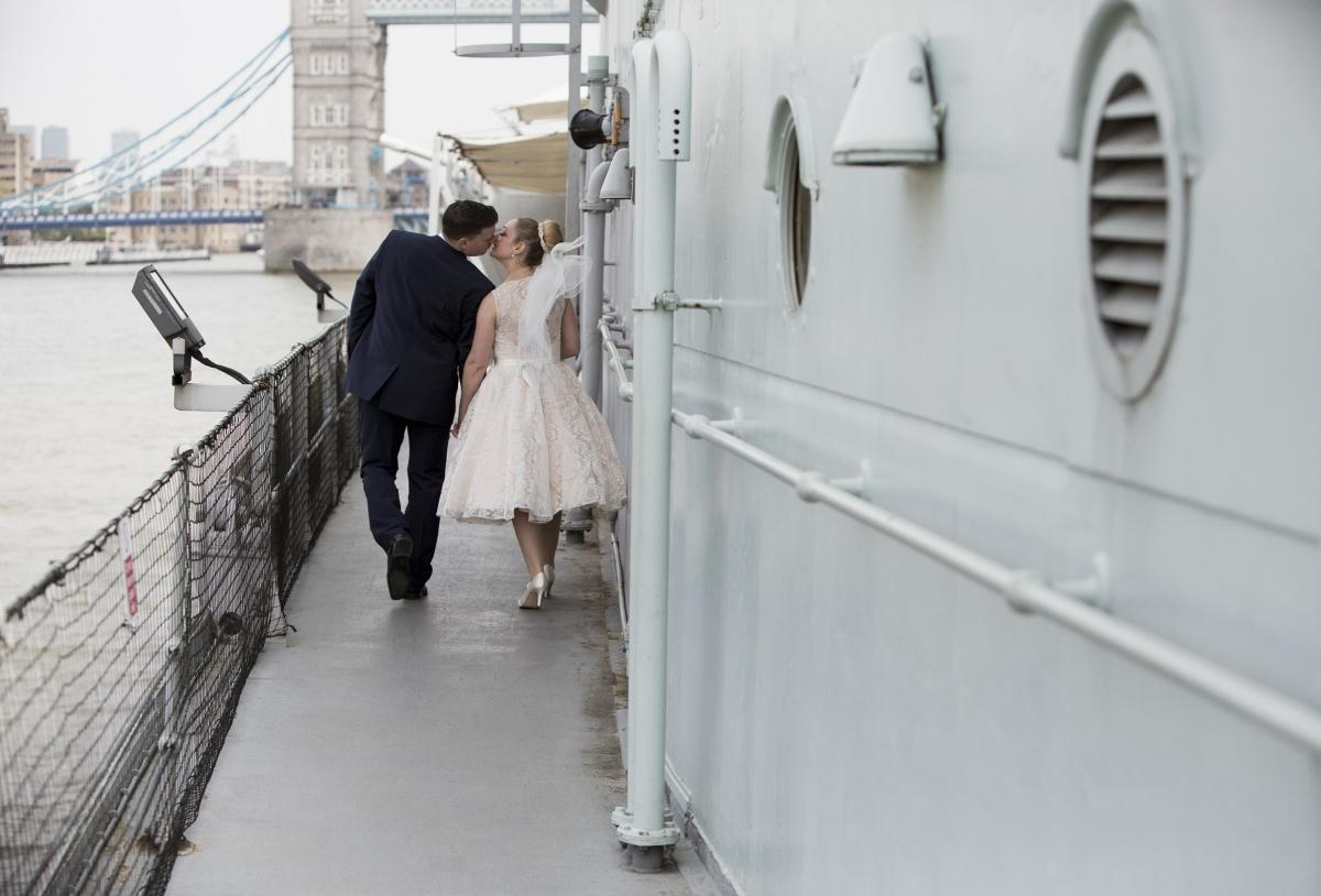 newlyweds kiss outside in the HMS Belfast ship.