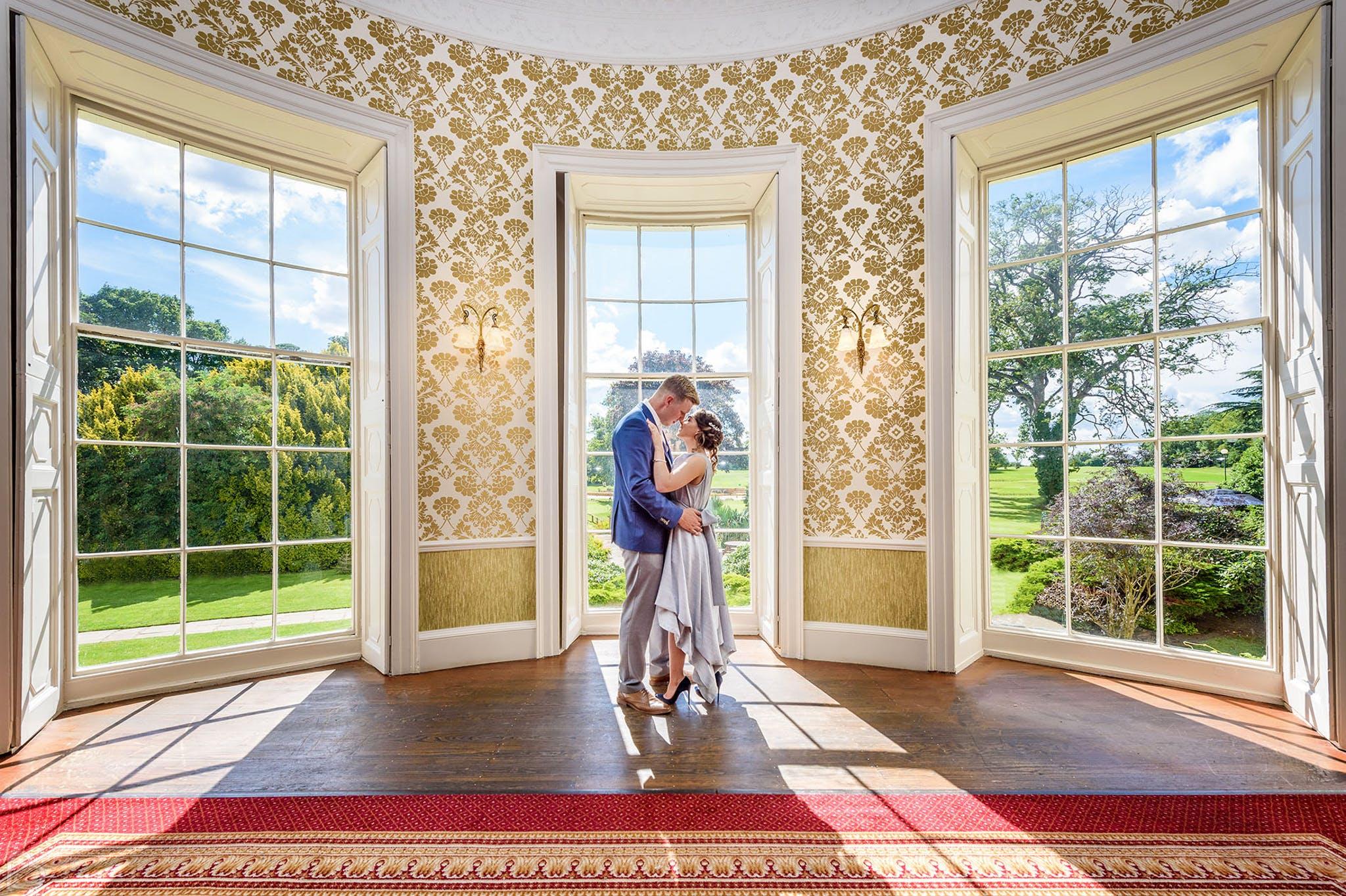 newlyweds kiss outside owston hall hotel.