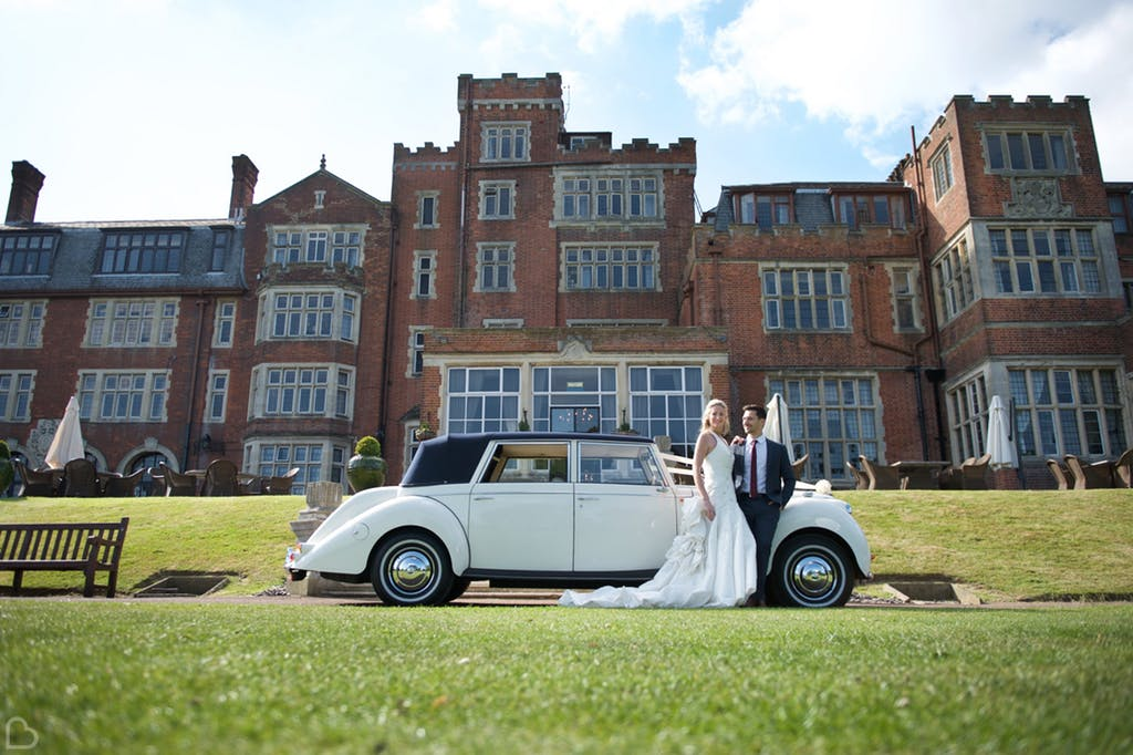 newlyweds pose with their classic car in front of seldsdon park hotel & golf club