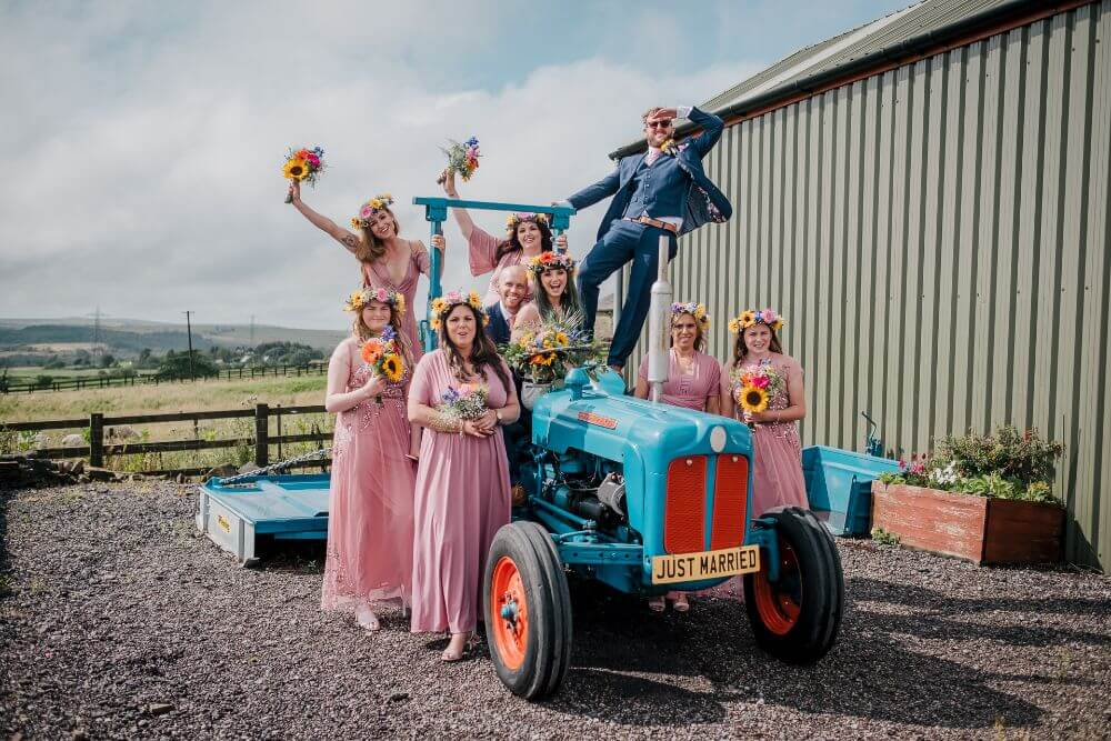 A wedding party (bride, groom, best man and bridesmaids) sat on a blue tractor with a 'Just Married' number plate.