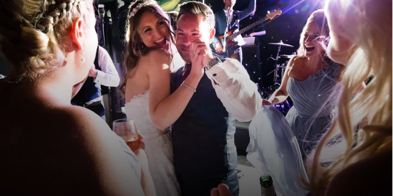 Happy newlywed couple on the dancefloor during their first dance with wedding music being performed in the background.