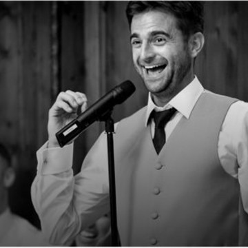 Smiling wedding toastmaster wearing a waistcoat and black tie giving a wedding speech