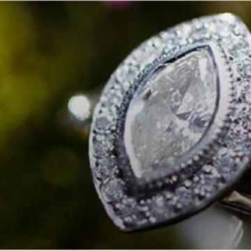 Stunning, oval shaped, diamond wedding ring against a green background.