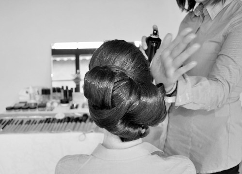 Back of a bride getting her wedding hairdo in a studio before the celebration