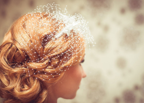 Profile of a bride with her hair done and covered in a white veil accessory