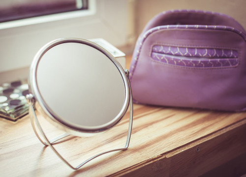 A wedding dressing table with a small round mirror and a washbag for brides to prepare before the ceremony