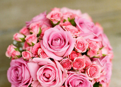 Round bouquet of big and small pink roses on a rustic wooden table for wedding decoration idea