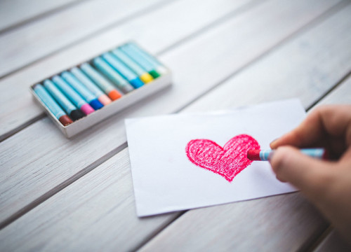 Hand drawing a red loveheart with pastel on white paper, on wooden table with pack of colourful pastel