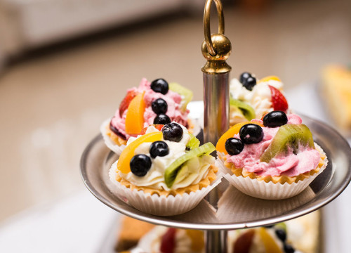 Top level of a silver cake stand holding fruit tartlettes for a wedding reception